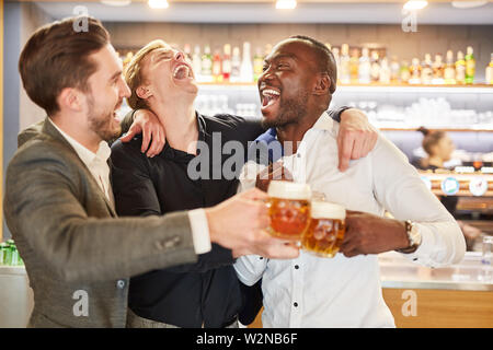 Friends on a men's evening having a beer in a pub or bar - Stock Image