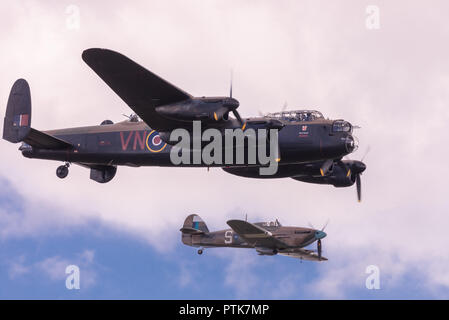 WWII Royal Air Force Avro Lancaster bomber escorted by Hawker Hurricane fighter at the IWM Duxford Air Show. - Stock Image