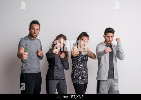Portrait of four joyful young friends with sportswear standing in boxing position. - Stock Image