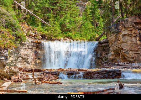 Waterfall flowing into Johnston Canyon creek at Banff National Park in Alberta, Canada. The waters empty into the Bow River. - Stock Image