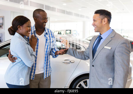 mid age car salesman handing over new car key to African couple in car showroom - Stock Image