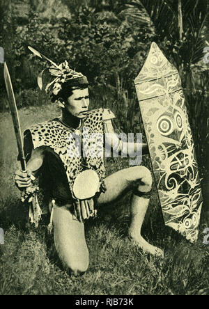 A Klemantan (Kalimantan) chief of Borneo, SE Asia (then part of the British Empire), wearing a tiger-cat war coat, and holding a sword and a shield. - Stock Image