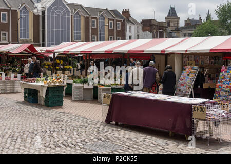 Shoppers browsing stalls on Northampton Market Square, UK; said to be one of the oldest and largest markets in England dating fro 1235. - Stock Image