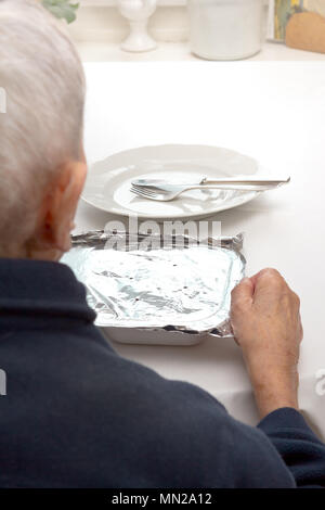 Old woman sitting alone at a table in her kitchen or living room with plate, cutlery and a precooked meal from a food delivery service - Stock Image