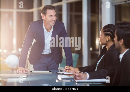 Businessman interacting with coworkers in a meeting in the conference room - Stock Image