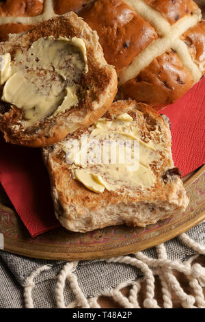 Hot Cross Buns toasted and buttered a spiced sweet cake traditionally eaten on Good Friday - Stock Image