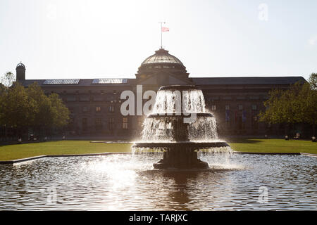 Fountain in front of the Kurhaus in Wiesbaden, the state capital of Hesse, Germany. The lawn in front of the historic landmark is known as the Bowling - Stock Image