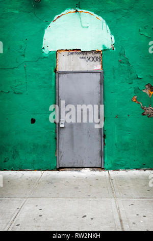 A mysterious rundown closed door on a side street in Corona, Queens, New York City. - Stock Image