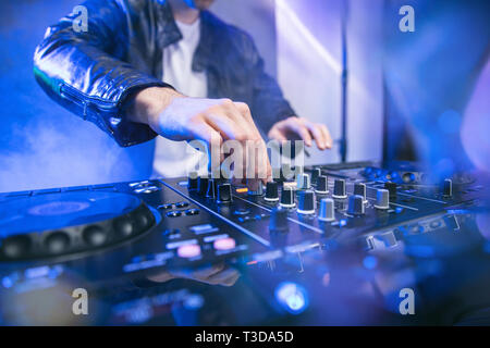 Dj mixing at party festival with blue lights and smoke in background - Summer nightlife view of disco club inside. Focus on hand - Stock Image