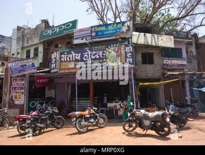 Commercial buildings, motor scooters and motorcycles in a small town in India - Stock Image