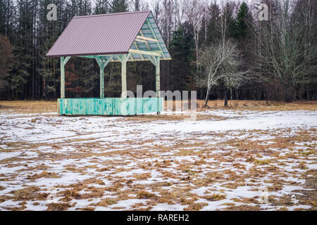 European bison and forest game empty feeding rack with metal roof in Bialowieza, Poland, partly snow, green hayrack, cloudy winter day - Stock Image