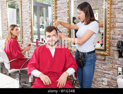 Young female hairstylist working with  male's hair  in hairdressing salon - Stock Image