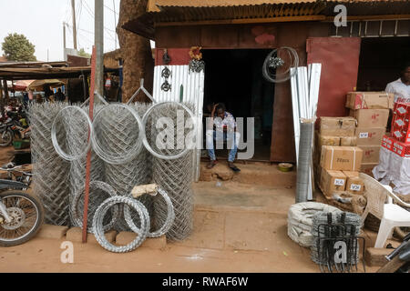 Small business in Africa: A man sits at a small business selling steel fencing wire and other metal products in Burkina Faso, west Africa - Stock Image