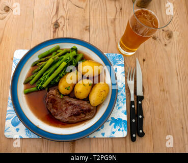 A fried Aberdeen Angus rump beef steak served with new potatoes, tenderloin broccoli and asparagus and gravy on a blue edged plate on a wooden table - Stock Image