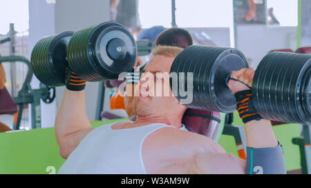 Athletic young man lifting dumbbells at gym - Stock Image