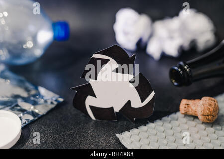 recycle symbol surrounded by reusable waste materials like plastic paper and glass, concept of reducing damage to the environment - Stock Image