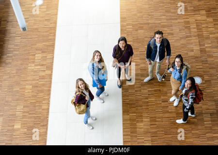 Male and female university students looking up from university lobby, high angle portrait - Stock Image