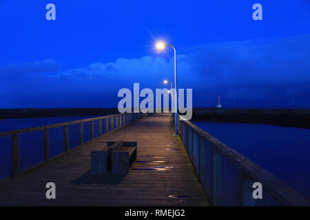Amble south pier at dusk  Looking down the south pier at Amble in the evening.  Amble is a small town on the north east coast of Northumberland - Stock Image