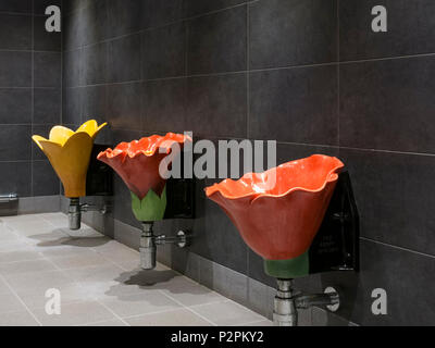 Row of three novelty flower shaped floral gents toilet urinals, UK - Stock Image