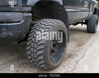 Low angle of black four wheel drive pickup truck showing the rugged front tire tread and wheel. - Stock Image