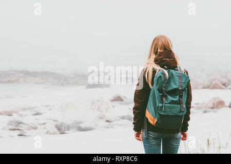 Woman backpacker standing alone outdoor Travel Lifestyle and melancholy emotions concept foggy nature on background - Stock Image