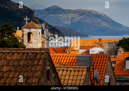View of rooftops, a tower with a cross and the coastline; Dubrovnik, Croatia - Stock Image