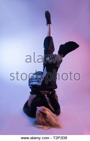 Attractive woman with legs in air and sports tracksuits shows his gymnastic skills on colorful background and studio red and blue lights. Low key - Stock Image