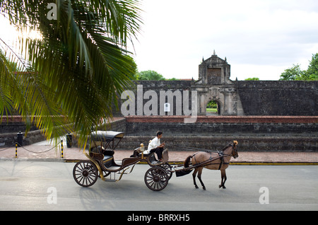 A horse and buggy pass the main gate of Fort Santiago in the historic Intramuros section of Manila, Philippines. - Stock Image