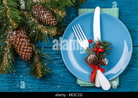 Christmas table place setting - blue table with green napkin, blue plate, white fork and knife, decorated sprig - Stock Image