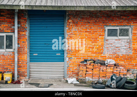 Old house, Brick wall and shutter door - Stock Image