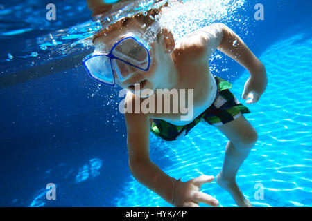 Boy swims underwater with snorkel mask - Stock Image