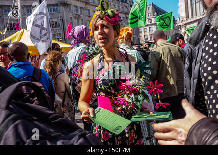 London, UK. 19th April 2019. People hand out fliers on Oxford St outside Oxford Circus station as police arrest protesters at Extinction Rebellion's Sea of Protest Police surrounded the yacht shortly after Emma Thompson spoke and put a cordon around Oxford Circus. They began persuading protesters to leave by threatening them with arrest and were cutting off those who were locked on around the bottom of the yacht. There were a number of arrests of protesters who refused to leave. A few tried to get the large crowd to protect the yacht, but XR organisers persuaded them not to physically oppose t - Stock Image