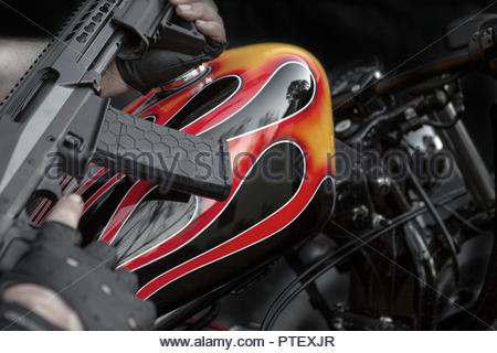 Modern Weapon Held Over a Custom Flame Painted Bikie Style Motorcycle - i - Stock Image
