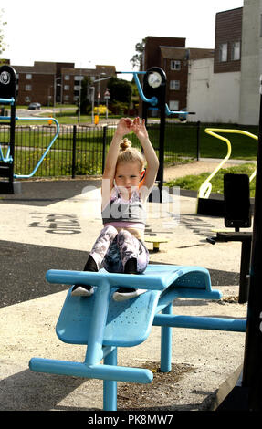 A six year old girl doing 'sit ups' on free to use equipment in an outdoor fitness area - Stock Image