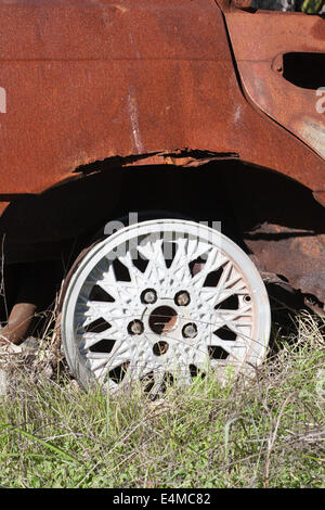 Alloy wheel on a burnt out, dumped and stolen car. - Stock Image