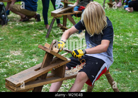 90th Kent County Show, Detling, 6th July 2019. A boy on a woodworking bench whittling wood. - Stock Image