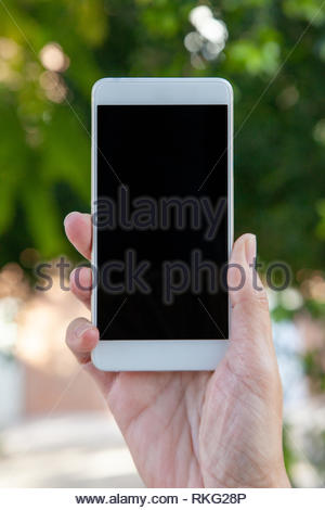 A female hand holds a white mobile with the empty screen in a vertical position in an outdoor location. - Stock Image