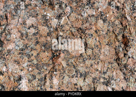Beautiful texture of red and black surface of a shiny rock. An interesting na​tura​l texture that can be used for example as a background or wallpaper - Stock Image