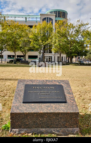 Commemorative marker and bronze statue to promote education in the advancement of commerce or business in a small city park in Montgomery Alabama, USA - Stock Image