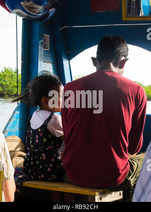 Helmsman's daughter sitting with him while driving tourist boat to see Kompong Stilted village on Tonle Sap Lake Siem Reap Cambodia Asia - Stock Image