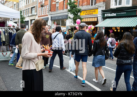 Woman on mobile phone cellphone texting whilst eating churros food on a London street with people UK - Stock Image