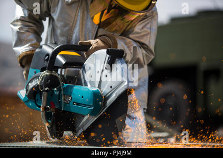 U.S. Marine Lance Cpl. Brandon Palmer, hand lineman, Aircraft Rescue and Firefighting (ARFF), Headquarters and Headquarters Squadron, Marine Corps Air Station (MCAS) Camp Pendleton, uses the K12 fire rescue saw to cut through metal during a gear drill at MCAS Camp Pendleton, Aug. 27, 2018. In a real scenario, the tool is used to break into a downed aircraft to save personnel trapped inside. (U.S. Marine Corps photo by Cpl. Emmanuel Necoechea) - Stock Image
