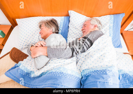 Couple of senior people married rest in bed, waiting for wake up. Happy retired caucasian man and woman - Stock Image