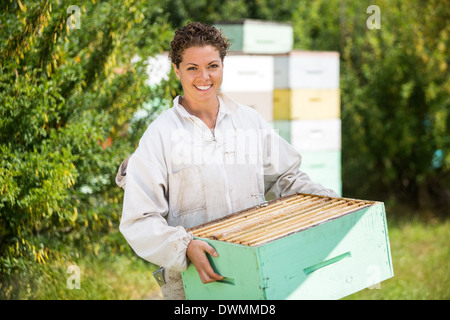 Female Beekeeper Carrying Honeycomb Crate - Stock Image