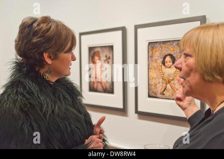 Huntington, New York, U.S. - March 1, 2014 - At right, artist LOIS YOUMANS discusses with a visitor the humorous artwork in Youmans' exhibit 'Vitreous Humor – A Collection of Absurd Images,' at the Opening  Reception '3 Wild & Crazy Artists' at FotoFoto Gallery. The images are a combination of photographs of dolls and vintage medical illustrations. - Stock Image