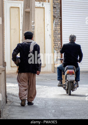 Yazd, Iran - March 7, 2017 : daily scene in a narrow alley of Old Town. Man riding a motorbike. Man holding a chicken - Stock Image