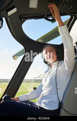 Female Pilot In Cockpit Of Helicopter Before Take Off - Stock Image
