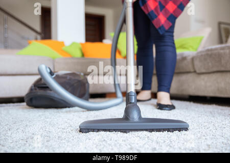 Woman is cleaning up the light grey carpet with vacuum cleaner with the couch on the background. - Stock Image