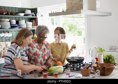 Active senior women cooking in kitchen - Stock Image