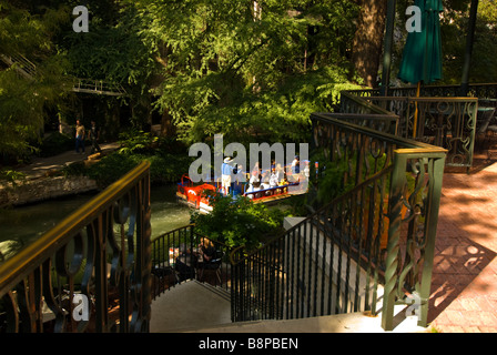 San Antonio River Walk riverwalk above tour boat with passengers passes row of stairs leading to river bank green - Stock Image